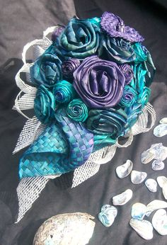Teardrop shaped wedding bouquet inspired by nz paua shell, turquoise blue and purple hand woven and dyed flax flowers with silver flax netting