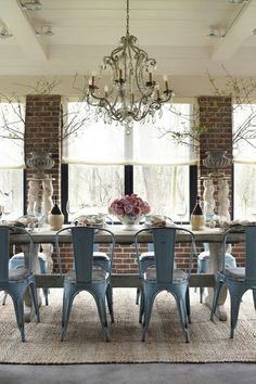 More tolix chairs. Love the slate blue, rustic table, brick walls, wood planked ceiling, and chandelier.