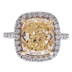 er, the ring is not wanting for detail either. Platinum framework with a 4.16 carat fancy yellow diamond at its center. The stone is GIA certified and exhibits Vs1 clarity. It is contained in an 18k yellow gold cup, with four 18k
