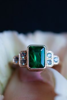 An emerald and sapphire engagement ring with a bezel set emerald cut green emerald center stone set in contrasting yellow gold. The unique custom ring was made to stand out as a bold, Art Deco inspired non-diamond engagement ring. A classic setting has vintage style milgrain around all stones. This emerald and sapphire engagement ring was custom made for and named after an Abby Sparks Jewelry client. #greenemerald #greenandgoldjewelry #customengagementring #gemstoneengagementring