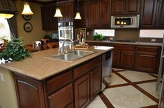 like cabinetry style. Needs to be lighter color. Countertop and fixtures are good. Need moulded backsplash and all smooth counter.  Sink and window combo a must.