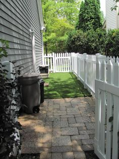dog run along side fence.... maybe small patch of fake grass in the run?
