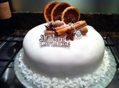 christmas cake decorated with dried oranges, cinnamon stick, almonds and star anise