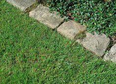 Avec des pavés de rue, Hubert le jardinier créé une bordure entre une allée gravillonnée et une pelouse.
