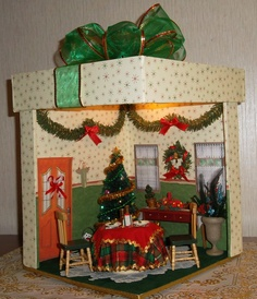 """My """"Merry Mini Christmas"""" in a gift box. I made it out of foam core 9X 12/12 inches. used scrapebook paper for the wallpaper and made the table used printies for the door and windows a few things were gifts from my dear friend Cheryl"""