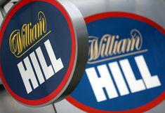 LONDON/SYDNEY (Reuters) – Paddy Power Betfair and William Hill have separately held talks about a deal with Australia's CrownBet as UK-focused gambling companies seek to expand overseas to offset tougher regulations in Britain.    FILE PHOTO: A branded sign is displayed outside a William ...