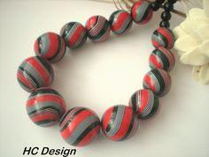 Červené spirálové...fimokorále... Velmi atraktivní masivnější náhrdelník složený z ručně modelovaných fimo kuliček o velikosti cca 2,3 -3 cm v červené, černé a bílé barvě. Leštěno. Kombinováno s dřevěnými korálky v černé barvě. Komponenty v barvě stříbra. Délka náhrdelníku je cca 52 cm + 5cm řetízek na prodloužení.