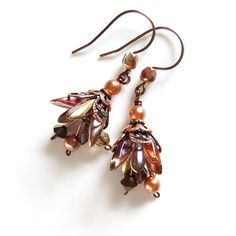 I made these delicate little drop earrings using Czech pressed glass dagger beads in lustred bronze, forming them into shimmery little flower