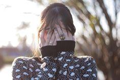 Mulher escondendo o roto usando um suéter preto com corações creme com a luz de fim do dia no Jardim Botânico de Curitiba.