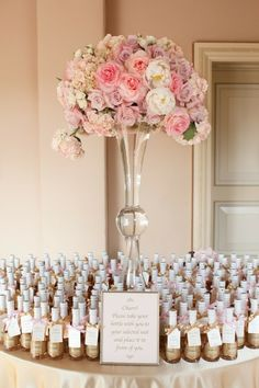 Table full of guest favors with tall centerpiece
