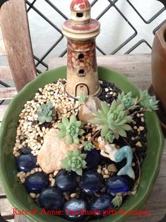 A miniature garden : Mermaid on the beach surrounded by succulents and a light house as her home