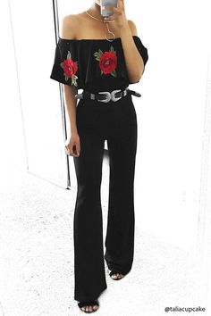 A textured stretch knit jumpsuit featuring an elasticized off-the-shoulder neckline, flounce ruffle neckline with floral embroidered appliques, short flounce sleeves, and a slightly flared leg.