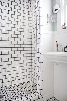 """Installed 1"""" Black and White floor Hexagon mosaic with 3""""x 6"""" Ceramic wall Subway tile with black grout."""