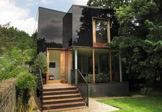 A newly built house in London, designed by Ian McChesney, that's completely clad in opaque black glass, reflecting the vibrant nature that surrounds it.