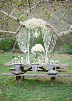 Crystals and natural wood.  A picnic bench sweetheart table has a rustic yet glamorous feel thanks to the silver and crystal details.