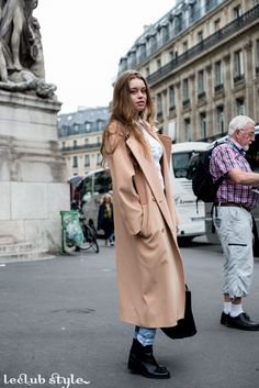 Womenswear Street Style by Ángel Robles. Fashion Photography from Paris Fashion Week. Oversized beige coat, denim and black ankle boots.