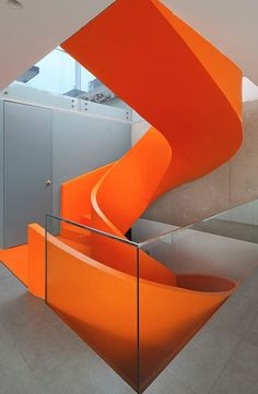 A fluorescent orange staircase spirals up through the center of this house that architect Martin Dulanto has completed in Lima, Peru. Named Casa Blanca, the house has a largely muted color scheme, with a white exterior, gray internal walls and some concrete surfaces. So the staircase becomes the most prominent feature in the building. The sculptural staircase connects all three levels of the small property.