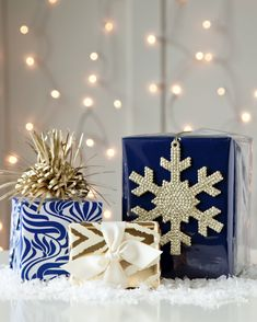 For this look we used every day wrapping supplies and simply added metallic for a festive look. The graphic, blue print is an every day wrapping paper found at Target, we call the topper 'sp…