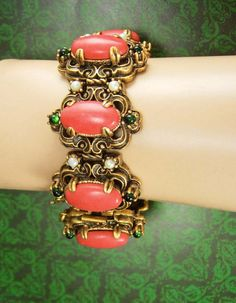 WOW ! WHAT a fantastic old bracelet ! It is really heavy and wide ( 1 1/4) and made with elaborate thick metal work that encompass these gorgeous
