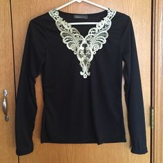 Black long sleeved top with sparkly ivory design Sharp long sleeved black stretchy top with sparkly ivory design around neck/ chest. Very flattering, however runs very small. Tag says medium but fits like a small or extra small. Never worn, NWOT Gamiss Tops Tees - Long Sleeve