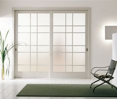 Modern interior sliding door featuring an inset acid etched glass panel with matte white lacquer frame