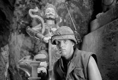 46. Marine Lance Corporal David L. Cruz tunes into the latest news on the Apollo moon shot on a helmet-mounted transistor radio while standing guard at Da Nang's Marble Mountain, on July 17, 1969. In background is a tall Buddhist figure found in many limestone caves of the mountain. (Ghislain Bellorget/AP)