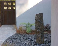 Use of large black gravel in this zen-like modern landscape design.