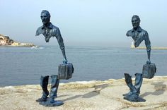 Esculturas de personas llevando una maleta con parte del cuerpo inexistente