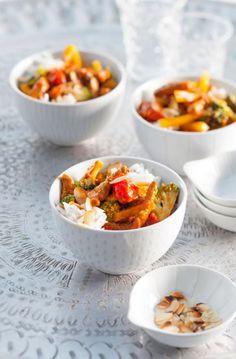 Recept voor Indiase varkenscurry met broccoli -300 g basmatirijst -400 g broccoli, in kleine roosjes -2 el olie -400 g hamlappen, in reepjes -1 gele paprika, in repen -2 el Indiase milde currypasta -2 blikken gepelde tomaten (à 400 g) -2 el amandelschaafsel