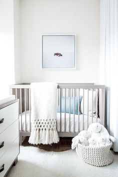 White and gray nursery features a gray crib, Oeuf Sparrow Crib, lined with organic cotton bedding as well as a blue pillow alongside a white cowhide rug atop a parquet wood floor.