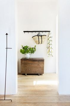 Wood dresser in mud room, hooks for hanging woven basket, and small plant