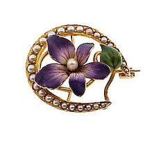 Art Nouveau 14K yellow gold honeymoon pin in the form of a pearl-studded horseshoe enclosing a beautifully-enameled violet.  In the Victorian language of flowers, the violet was used to symbolize faithfulness. Combined with a horseshoe for good luck, a pin of this sort almost certainly would have served as a going-away gift. The original clasp is stamped 14K and has Krementz' hallmark.