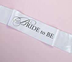 This white satin sash is designed for the future bride at her bachelorette party, with transfer artwork in black that reads Bride to Be. The sash is 68 long and 5 wide. The ends of the sash are sewn together. Bachelorette Party Sash, Bachelorette Party Supplies, Bachelorette Ideas, Wedding Sets, Trendy Wedding, Wedding Dinner, Lillian Rose, Bride To Be Sash, Wedding Shoppe