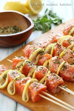 Salmon cubed, and skewered with lemon slices and herbs.