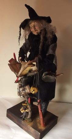 Handmade Folk Art Witch By Kim Sweet~Kim's Klaus~Handmade Leather Spell Book Resting upon Tree Branch~Branches Hold dripping Candles~Rusty Key~Clay Jack-O-Lantern~Clay Skeleton Head~Potion Bottle~Handmade Clay Black Scaredy Cat At her side...handmade Broomstick leans on the Branch