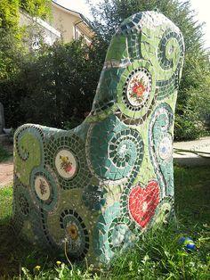 Started with a regular metal garden chair, covered it with chicken wire and concrete, and then added the mosaics.
