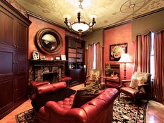This traditional man's library is filled with rich leather and wood furniture. The antique map ceiling draws the eye upward, while the red Venetian plaster walls add texture. Soft lighting leaves a calm feeling in the room, and the floor-to-ceiling draperies and area rug tie all the colors of the room together. Design by Jennifer Duneier