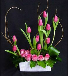 Pink tulip and rose flower arrangement with willow branches.