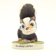 """SOLD - Pre-owned decorative collectible matte bisque porcelain ceramic skunk.  The skunk appears to have a clothespin on its nose and the words """"But Nobody's Perfect"""" are on the outside edge of the base."""