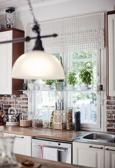 white kitchen, brick wall, green plants.