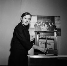 """Frances Oldham Kelsey, FDA scientist who kept thalidomide off U.S. market, dies at 101. In this photo she examines scales, in Washington, D.C., ca. Oct. 16, 1962, used by the Agency's first head, Dr. Harvey W. Wiley, to measure doses for his """"Poison Squad,"""" established in 1902. Wiley and his squad are pictured in photo on the wall."""