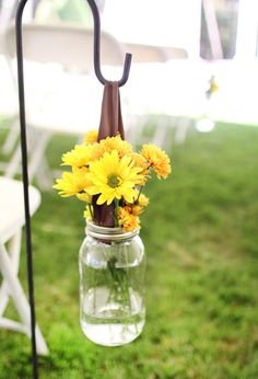 Gerbera daisies in mason jars.Good idea for an outside wedding