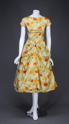 Floral-print dress worn by Audrey Hepburn in 'Funny Face' (1957). The floral dress has orange, yellow and white flowers against a yellow background with delicate green leaves, bateau neckline with short sleeves, a layered skirt with slight apron at hips.