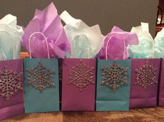 Frozen theme goody bags! Each bag contains hot chocolate, marshmallows, a chocolate/peppermint stirrer and a soft fluffy pair of gloves! I attached a snowflake ornament to complete the look!