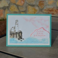 DIY seaside card with watercolored cliff and lighthouse.  Pink clouds and lovely sentiment.  Ocean has stamped texture and embossed foamy, white caps with water spray.