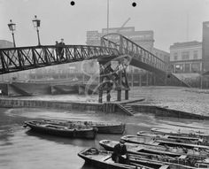 Limehouse Pier, Poplar, London, A bridge leads to the pier looking towards Dundee Wharf and Horn and Chequers Public House with barges resting on the mud and a man sitting in a rowing boat on. London History, British History, Vintage London, Old London, East End London, Sailing Regatta, Man Sitting, Beach Landscape, London Street