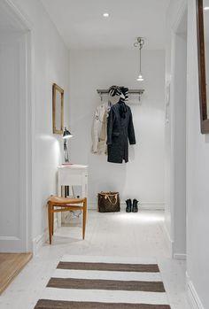 Biały skandynawski przedpokój ocieplają dodatki – drewniane ramy luster i taboret ze skórzanym siedziskiem. W naturalnej kolorystyce jest utrzymany także plastikowy chodnik w brązowe pasy. Dzięki wyrazistej fakturze splotów dodaje wnętrzu przytulności.