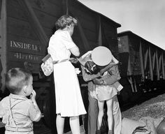 """The Omaha World-Herald's 1944 Pulitzer Prize winner """"Homecoming"""" photograph taken by Earle L. """"Buddy"""" Bunker. In the photo, taken in Villisca, Iowa, on July 15, 1943, Lt. Col Robert Moore is greeted by his wife, Dorothy Dee Moore, and daughter Nancy, 7. At left is a young nephew Michael Croxdale.   Like anything you see? Email owhstore@owh.com or call 402-444-1014 to purchase prints."""