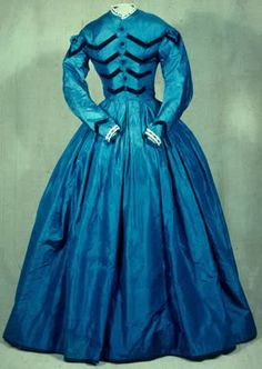 Looks like a civil war era dress - would make a great costume and long sleeves would certainly be helpful in winter weather.