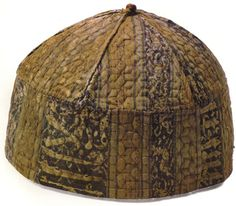 This 14th c cap is surmounted by a small ball bound with red thread.  The outer layer is pattern-woven (possibly lampas weave) silk fabric. The lining is woven of a bast-like fiber.  The pieces appear to have been quilted before they were sewn together. The quilt pattern of lozenges, stitched in red thread, can be viewed as overlapping six-pointed stars.  by men, women, and children in Mamluk Egypt.  Cairo Museum in Egypt (Is tagging correct? or Cleveland?)